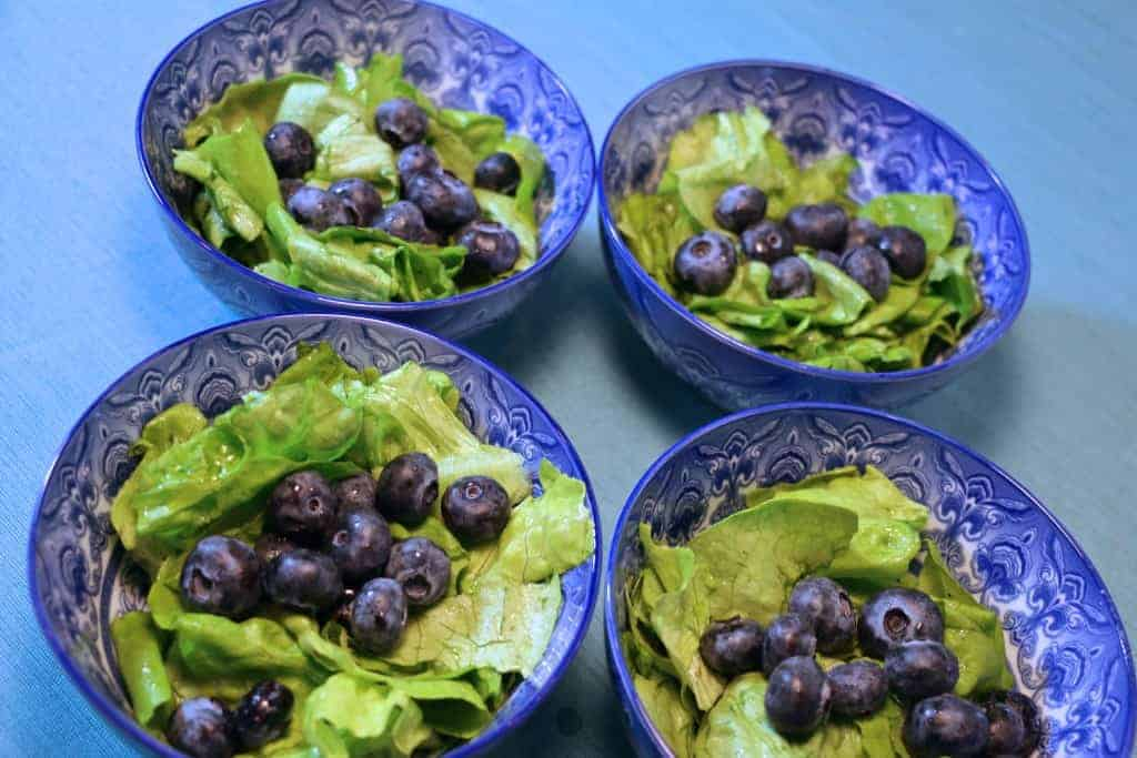 Blueberries added to the 4 salad bowls