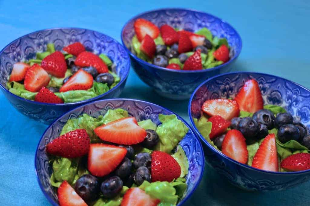 Strawberries added to the 4 salad bowls