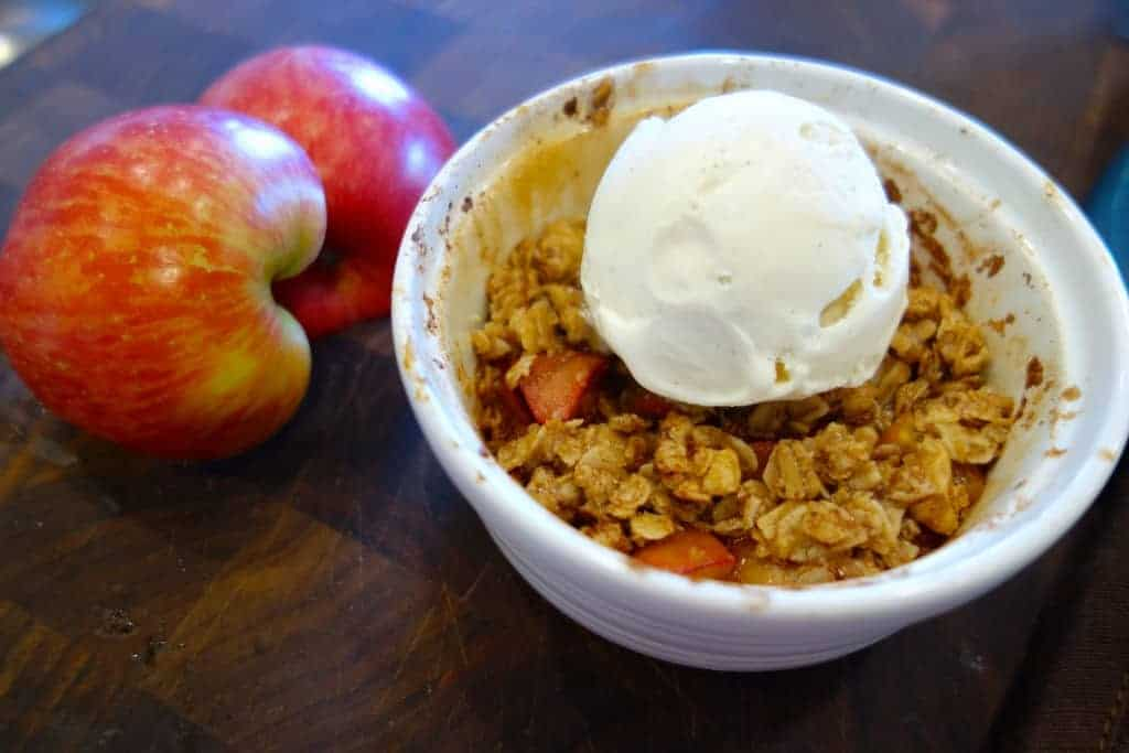 Single serving apple crisp in a ramekin with vegan ice cream next to decorative apples