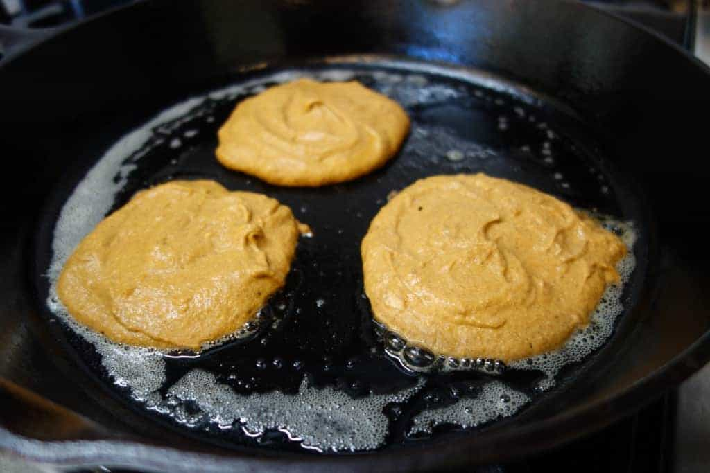 Pumpkin pancakes cooking on a cast iron skillet