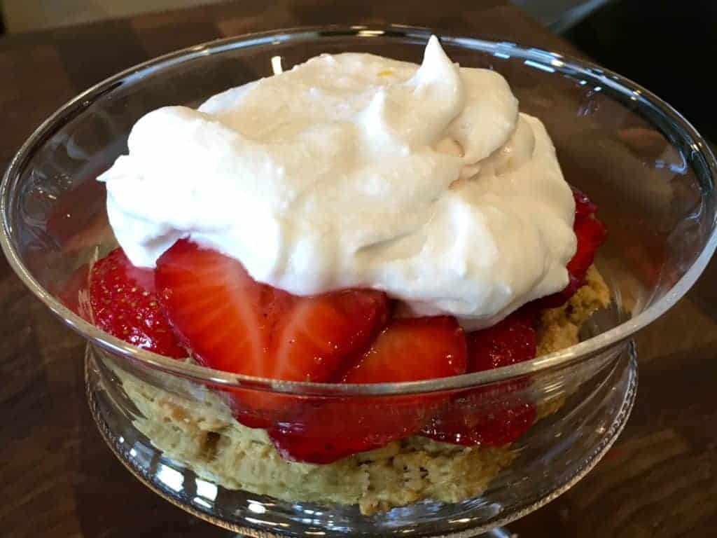 Lemon whipped cream on top of strawberries and biscuit in glass serving dish