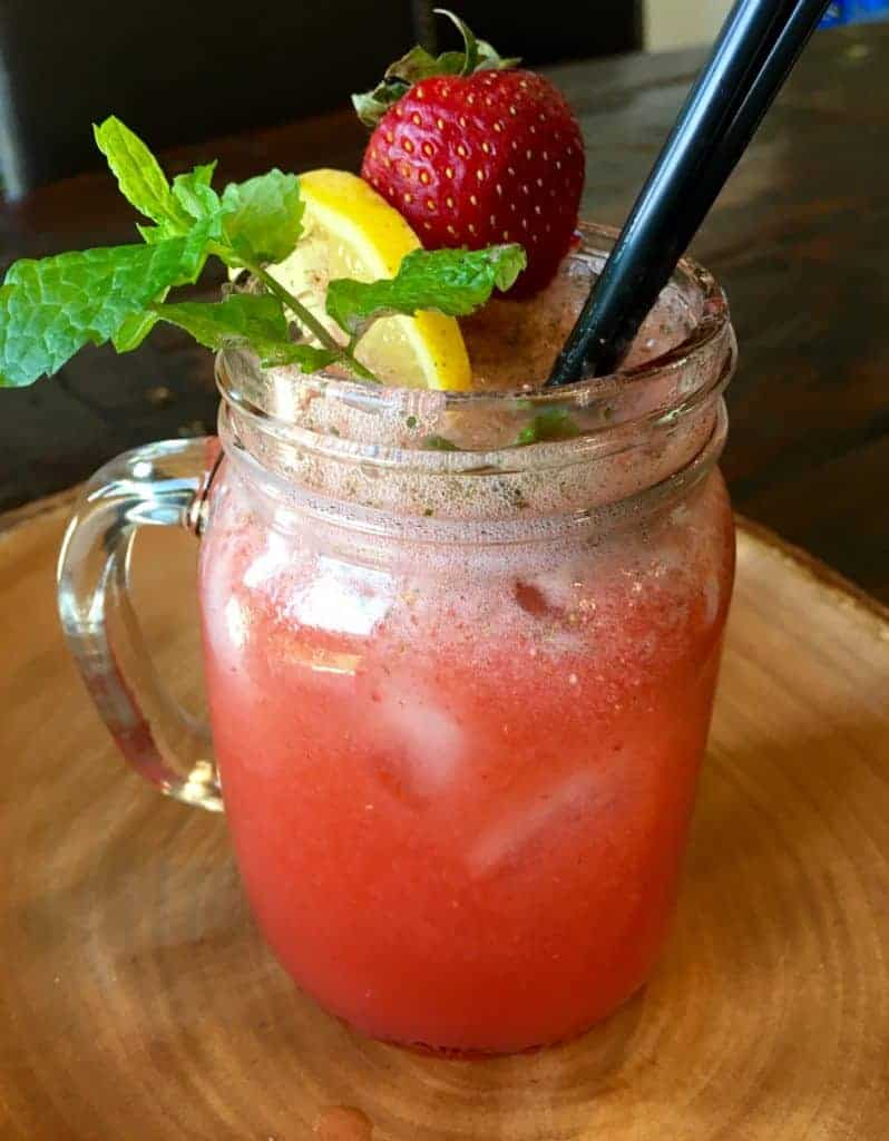 Strawberry Mint Lemonade in a mason jar with strawberry and lemon garnish