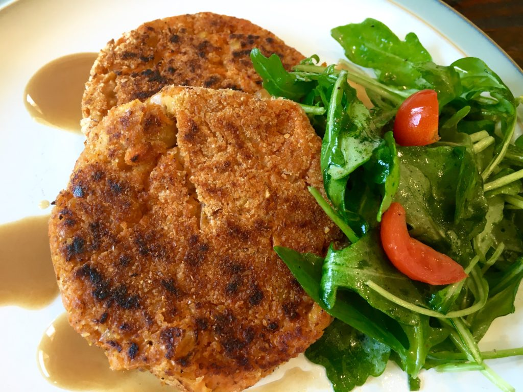 Sweet potato bean burgers on a plate with a salad and no bun