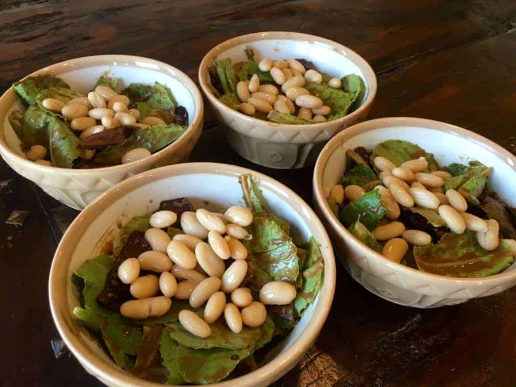 Lettuce, beans, and dressing in four ramekins