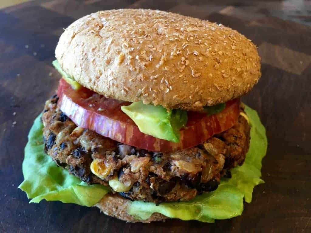 Southwest Black Bean Burger on a bun with lettuce, tomato, and avocado