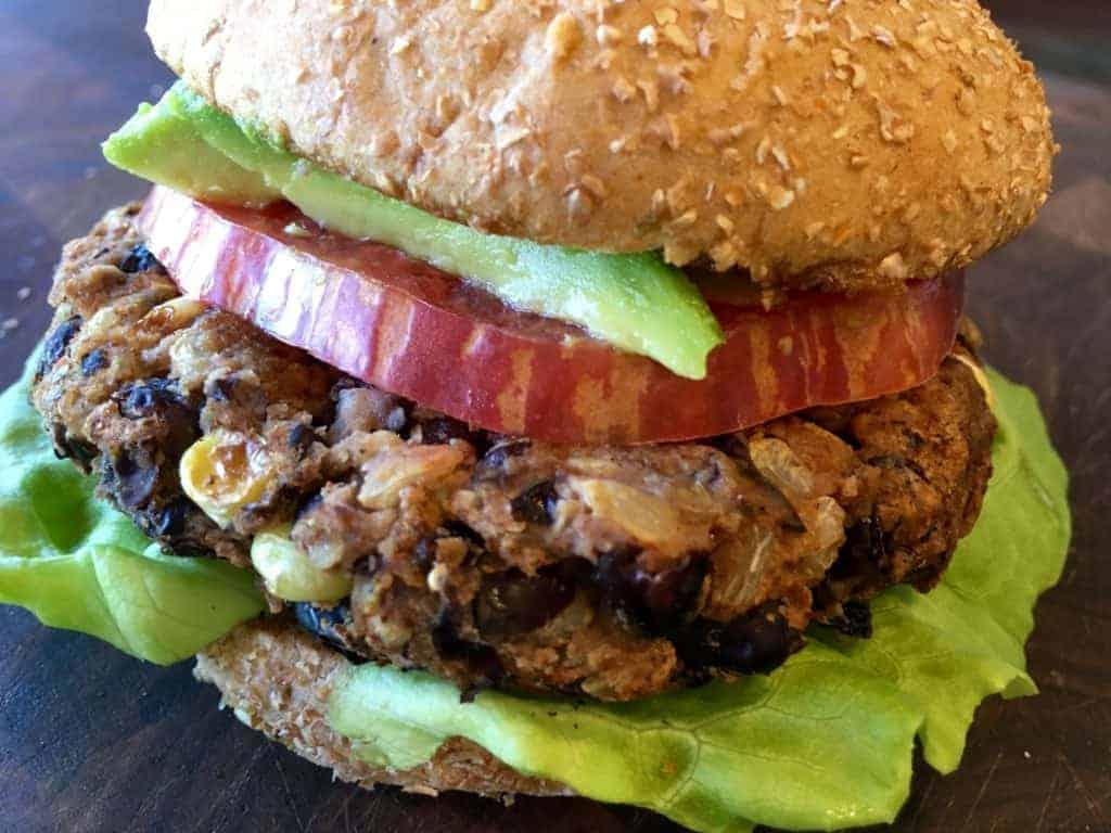 Easy Southwest Black Bean Burger on a bun with lettuce, tomato, and avocado