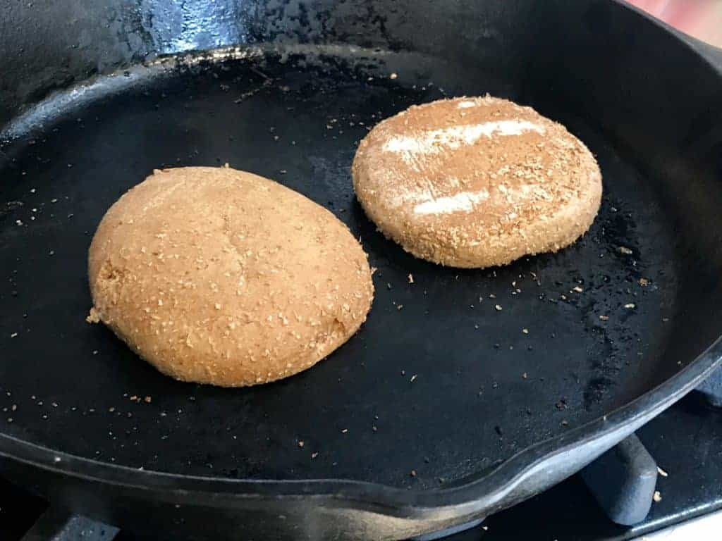 Hamburger bun toasting on a cast iron skillet
