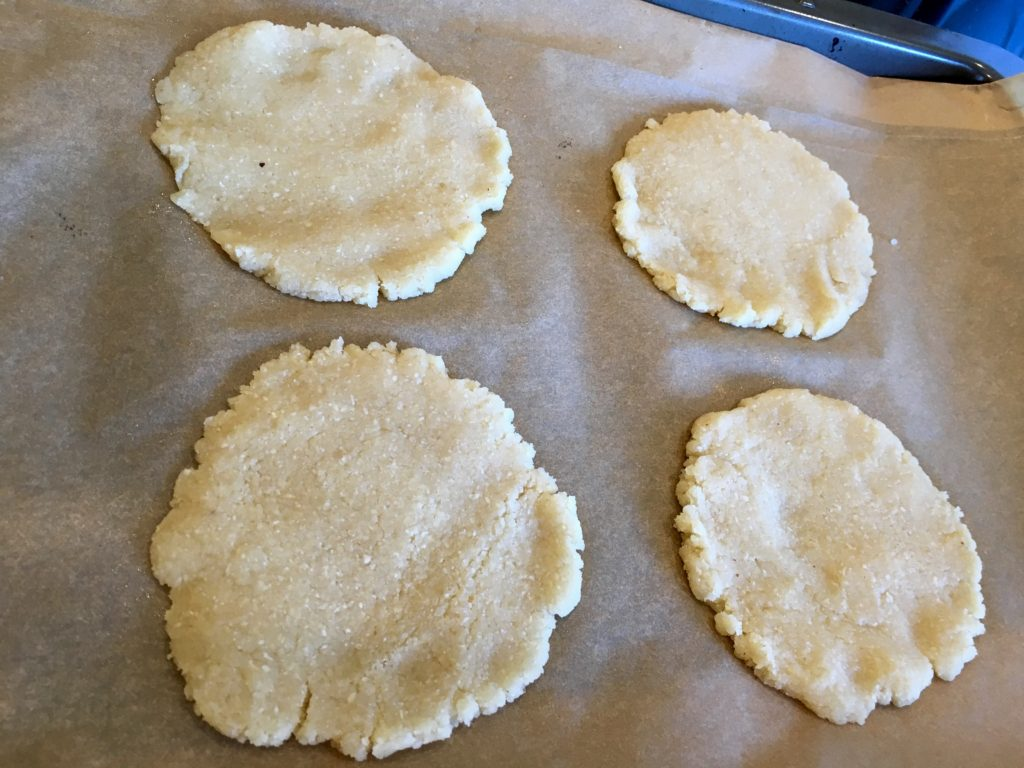 4 raw pie crusts flattened out in a circle on a baking sheet with parchment paper