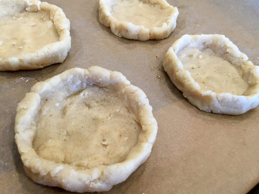 Raw pie crusts on a baking sheet with edges pinched up