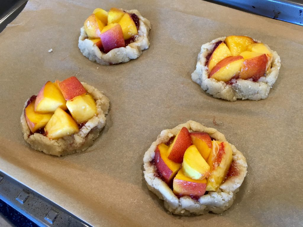 Chopped peaches inside the raw pie crusts with jam
