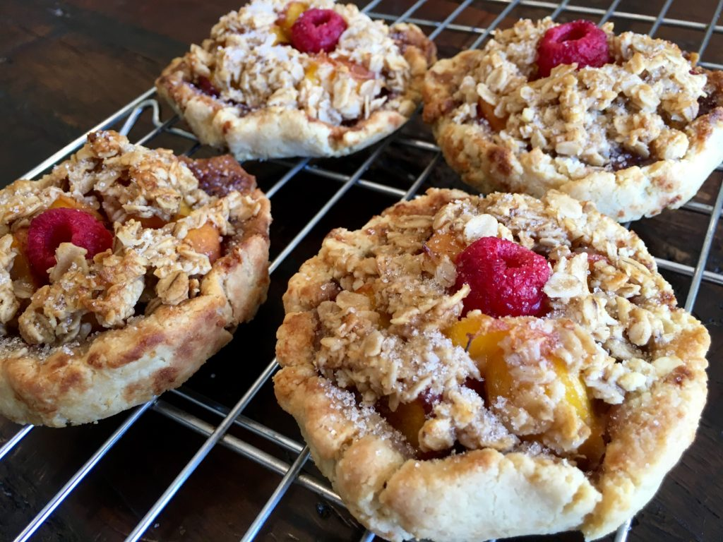 Baked Peach Raspberry Pies on a cooling rack