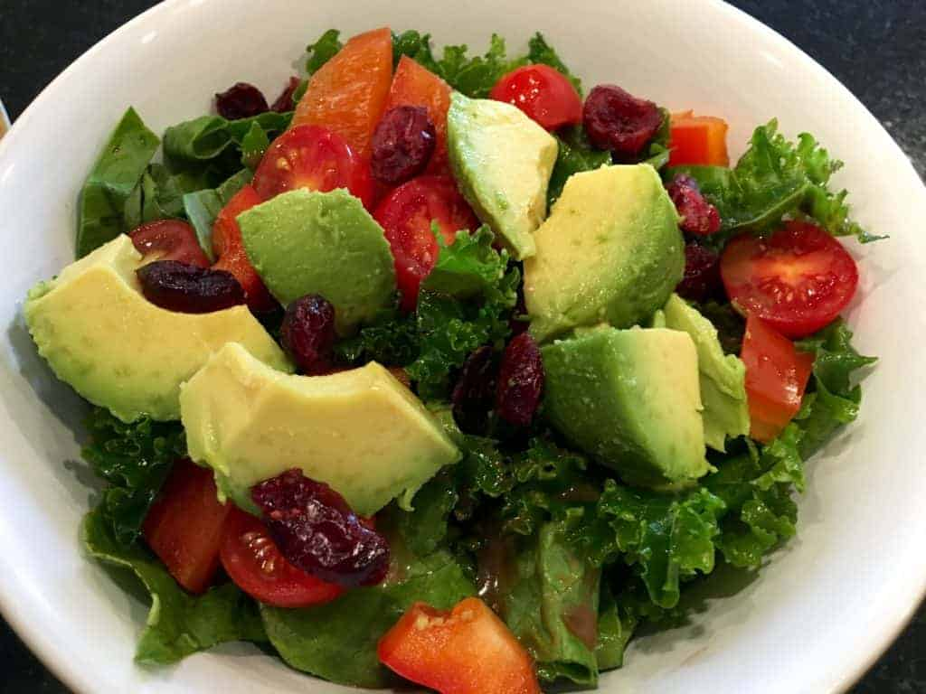 Kale salad with avocado, tomatoes, and dried cranberries