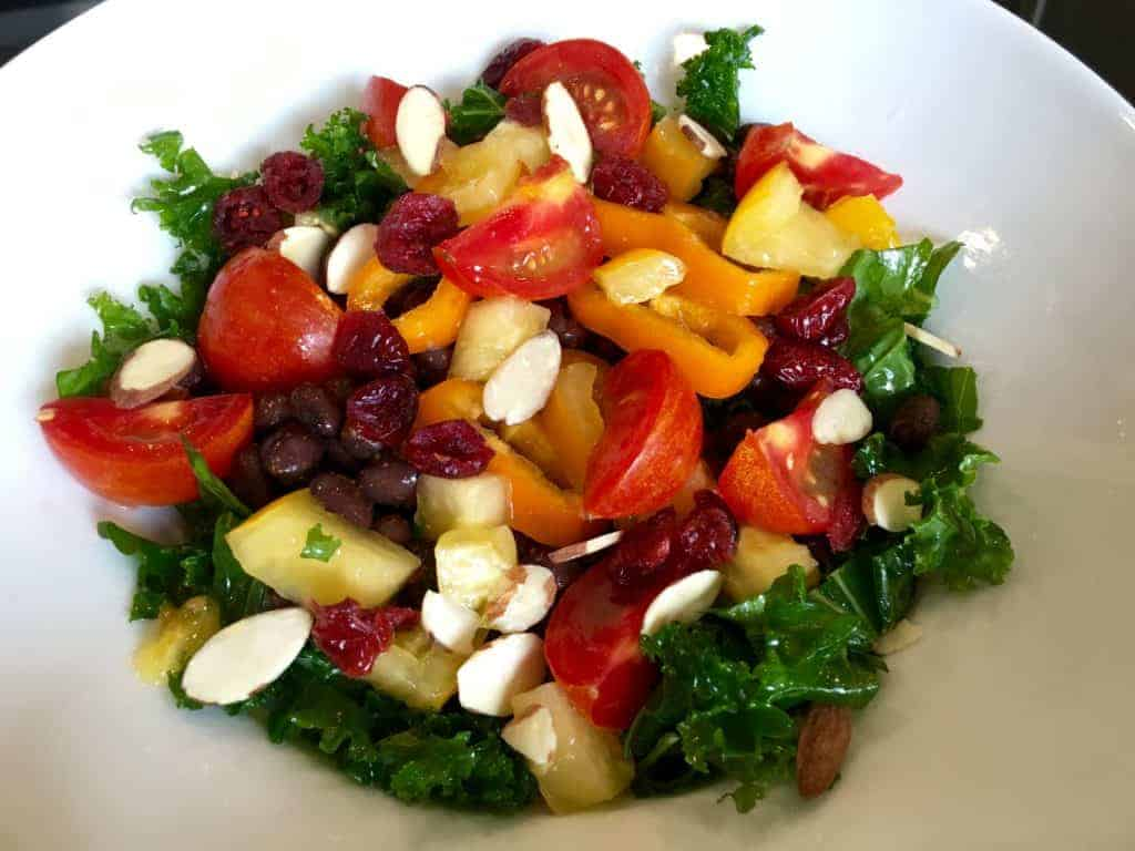 Sweet and tangy lemon dressing on a salad with kale, tomatoes, peppers, nuts, and dried cranberries