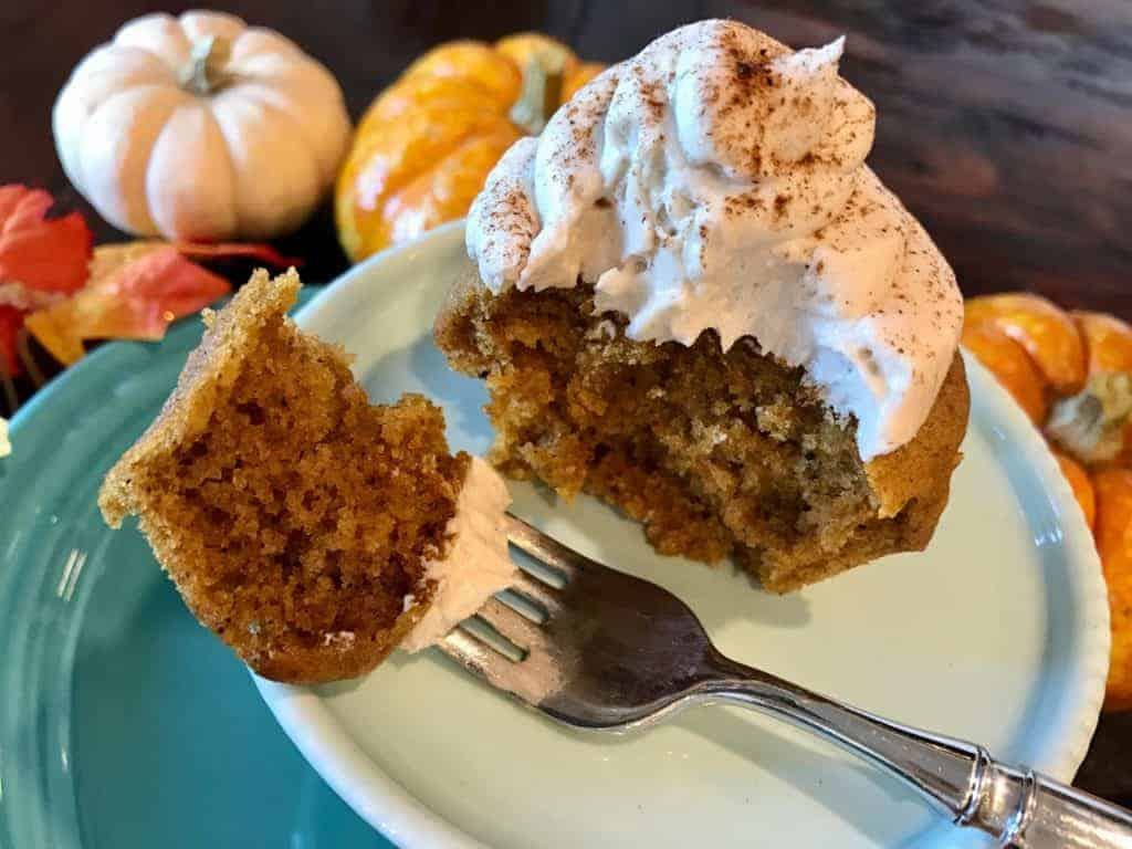 Pumpkin spiced cupcake with maple frosting on a plate with a piece on a fork