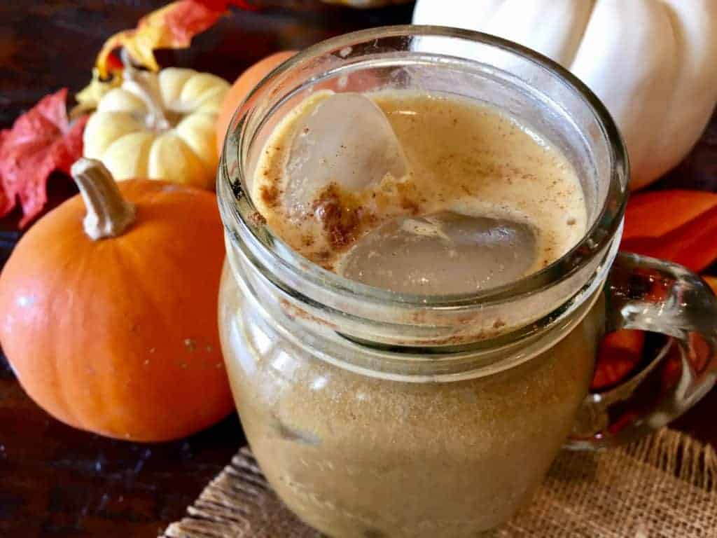 Vegan pumpkin spiced iced latte in a mason jar on a table in front of decorative pumpkins