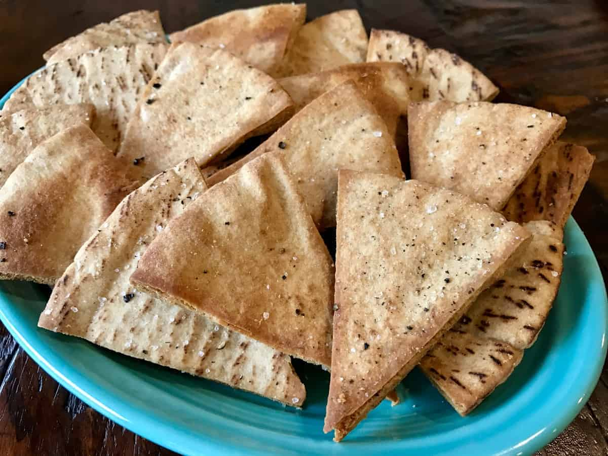 Crunchy salt and pepper pita chips on a blue plate