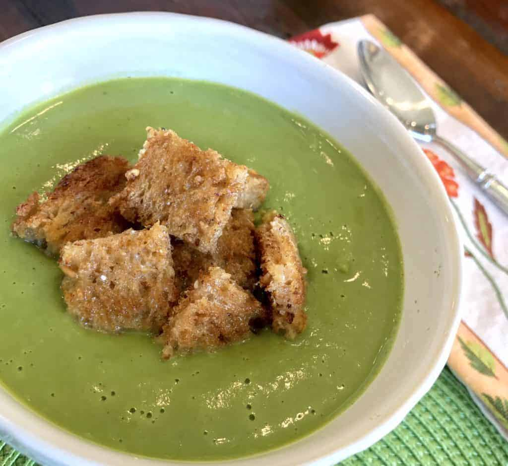 Easy vegan super greens soup in a bowl with croutons on a table