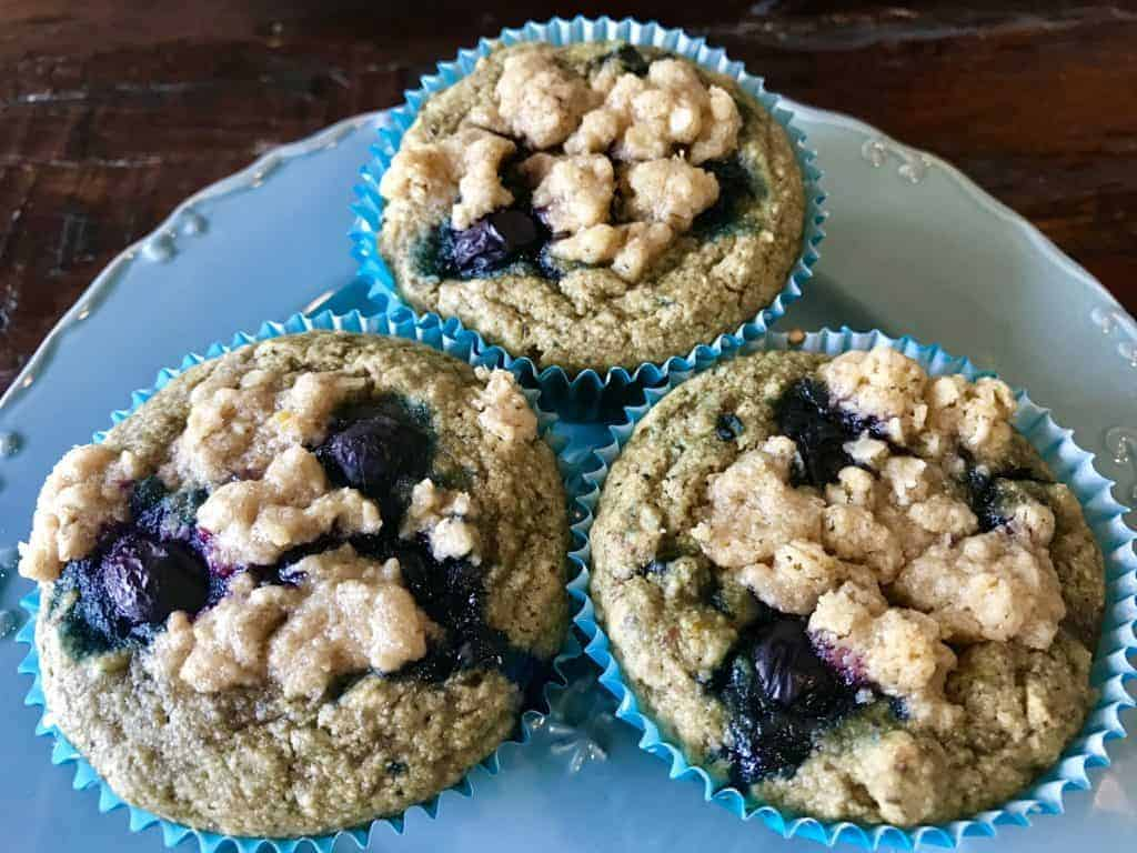 Three vegan lemon blueberry muffins on a blue plate