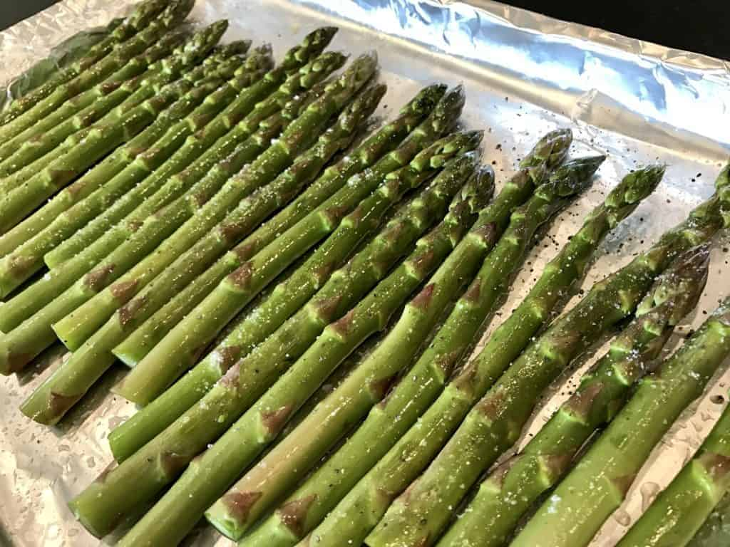 Raw asparagus on a baking sheet with olive oil and sprinkled with salt and pepper
