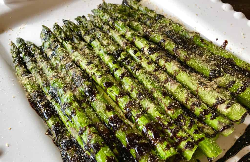 Roasted Asparagus with Balsamic Glaze on a white plate