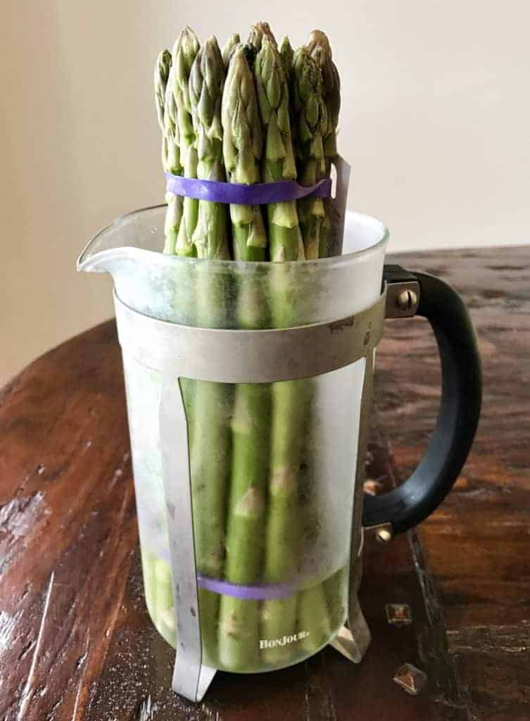 A bunch of asparagus in a french press with water