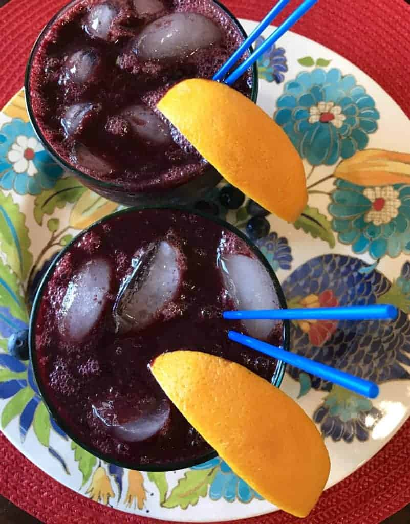 Two blueberry margaritas garnished with oranges and blue straws