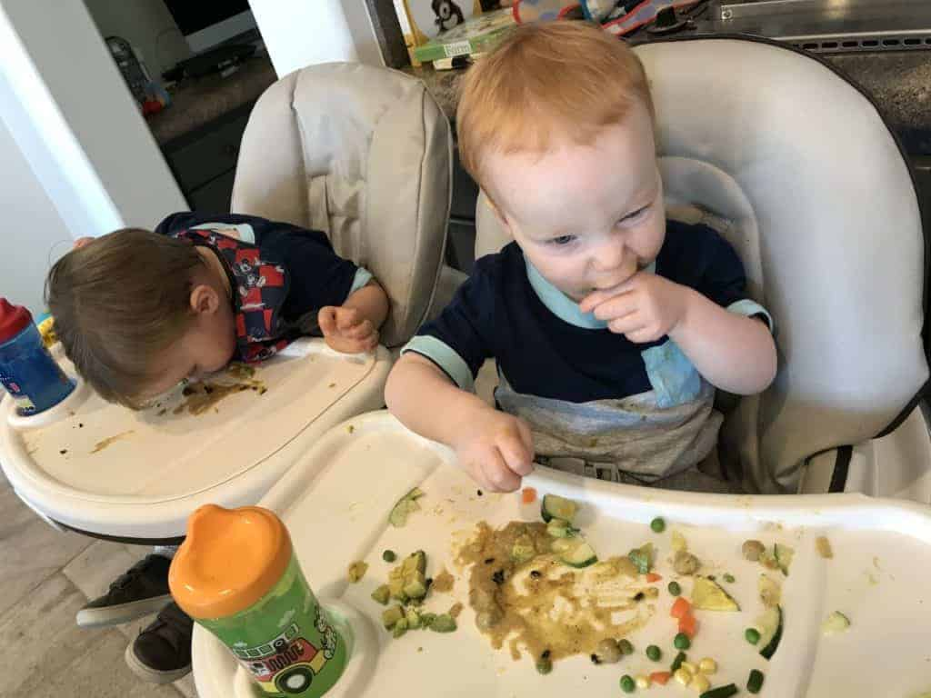 Jack and James eating Coconut Curry Vegetables in their high chairs