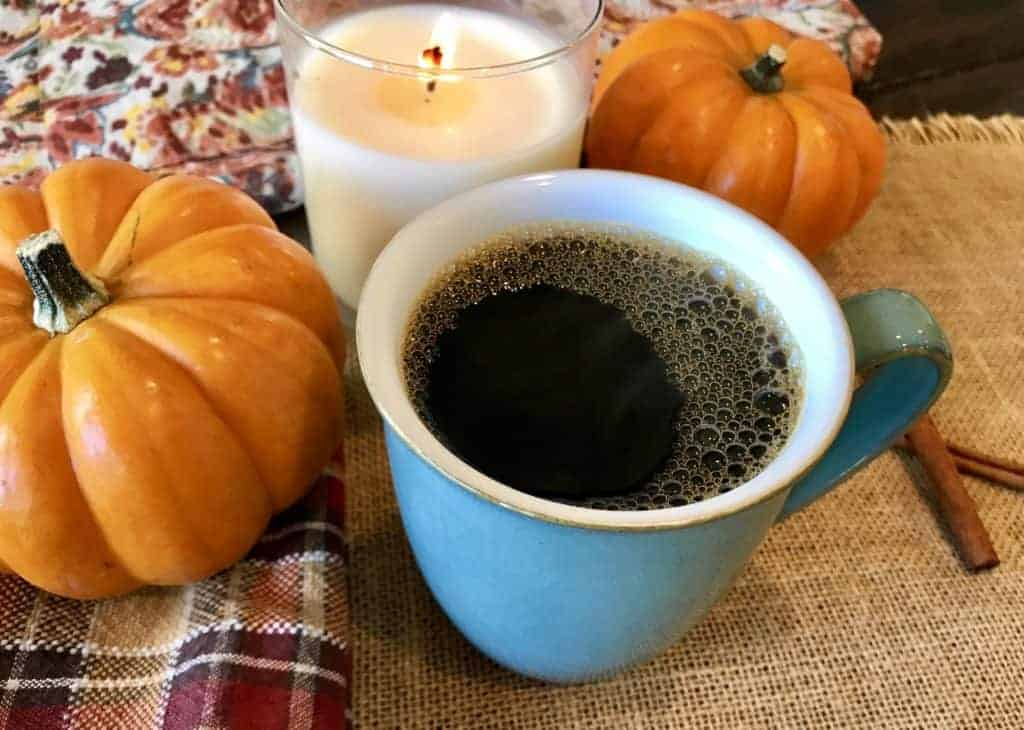 Pumpkin spiced coffee in a mug on a table next to a candle and decorative pumpkins