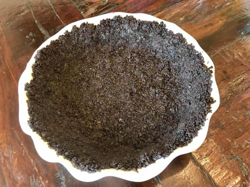 Oreo cookie crust pressed against a pie pan