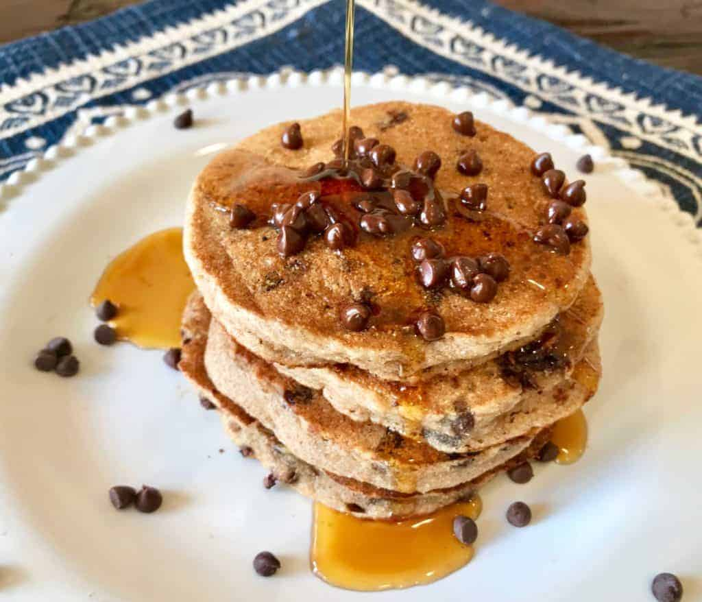 Vegan Chocolate Chip Whole Grain Blender Pancakes on a plate with maple syrup pouring on it