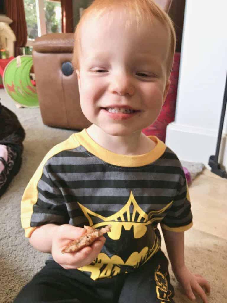Jack Dunham holding a vegan chocolate chip whole grain blender pancake and smiling