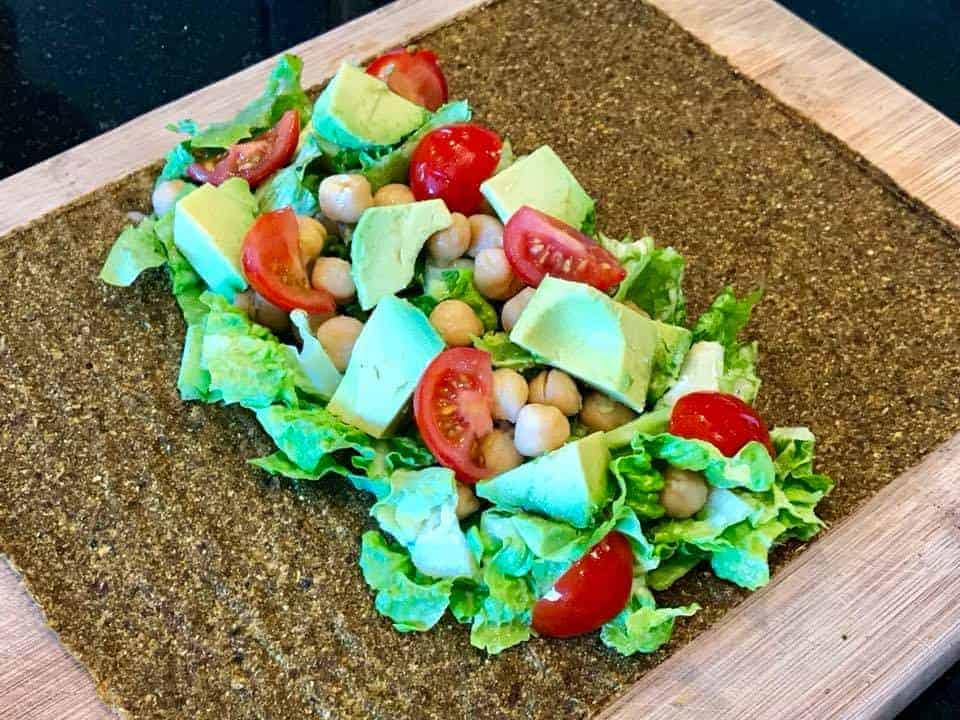 Lettuce, tomatoes, avocados, and chickpeas in the middle of a wrap