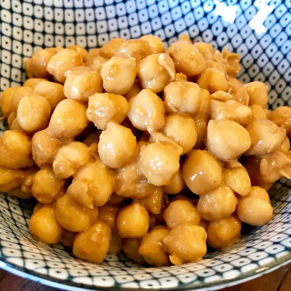 Peanut butter and coconut aminos mixed with chickpeas in a bowl