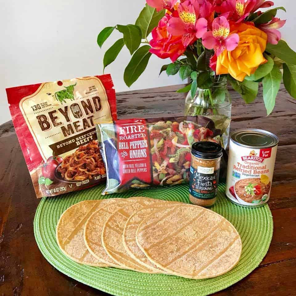 Ingredients for 5-Ingredient Vegan Fajita Tacos on a table with flowers