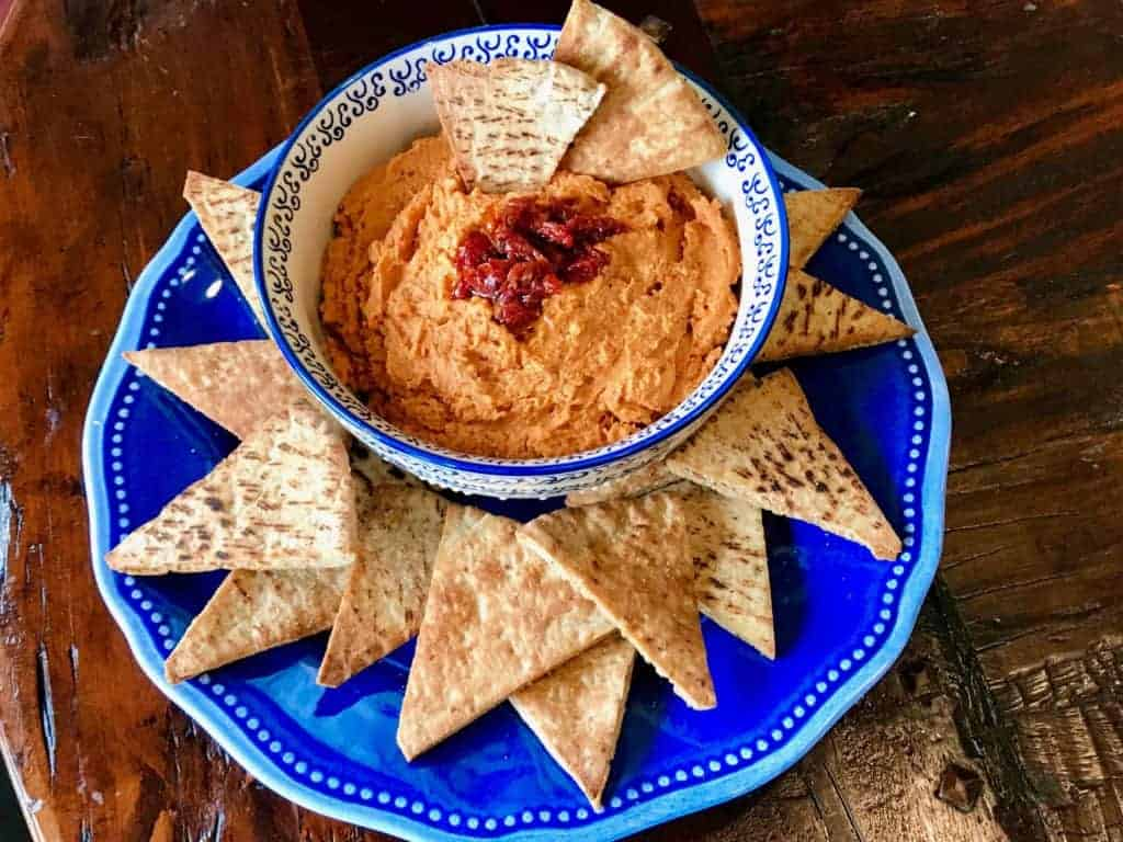 Sun-dried tomato hummus in a bowl with pita chips