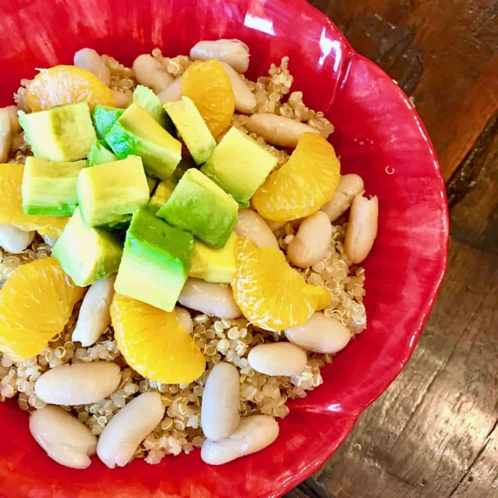 Bowl of quinoa, beans, and mandarin oranges topped with avocado