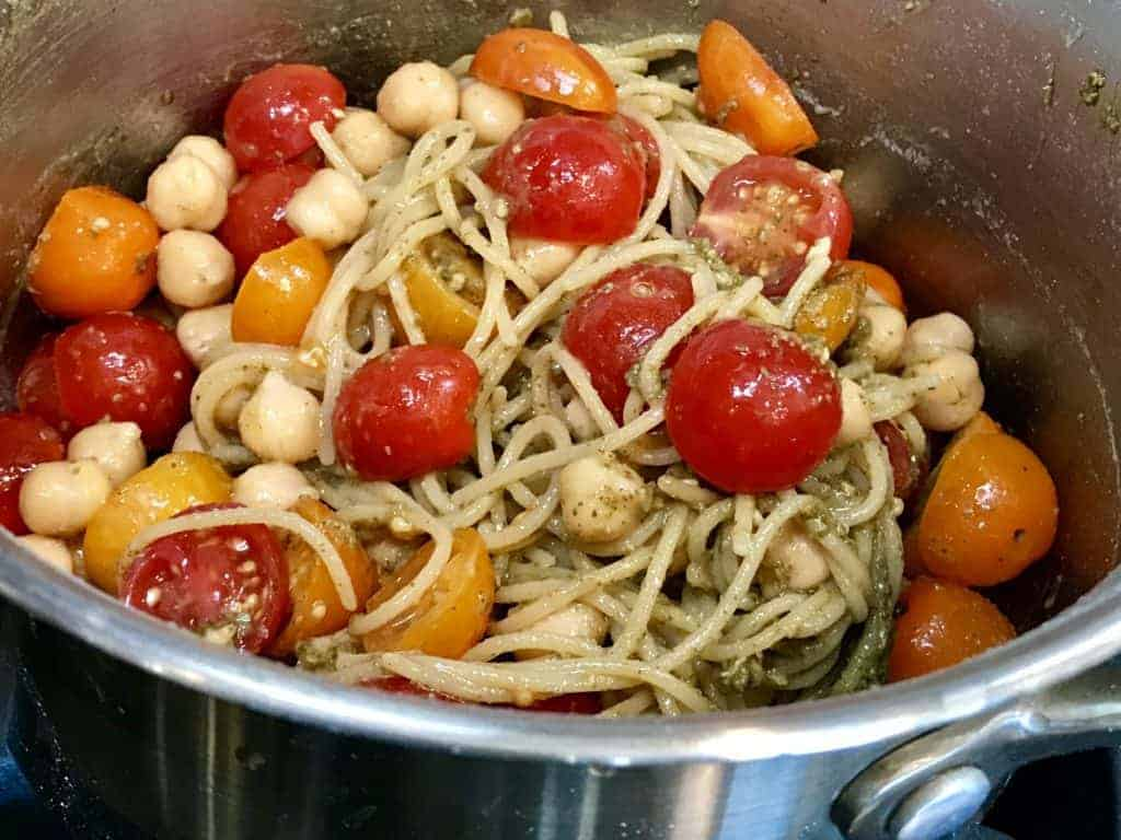 Tomatoes, pesto, and chickpeas added to pot on the stove