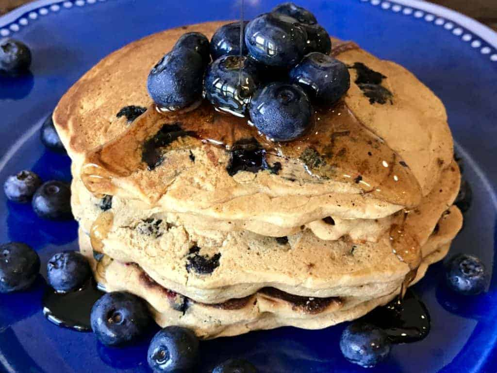 Stack of vegan and gluten free blueberry pancakes on a plate with syrup