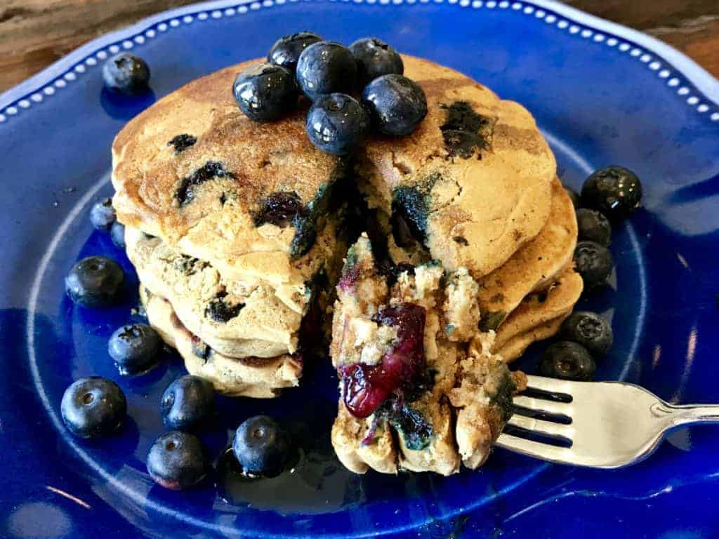 Stack of the best vegan and gluten free blueberry pancakes on a plate with a bite on a fork