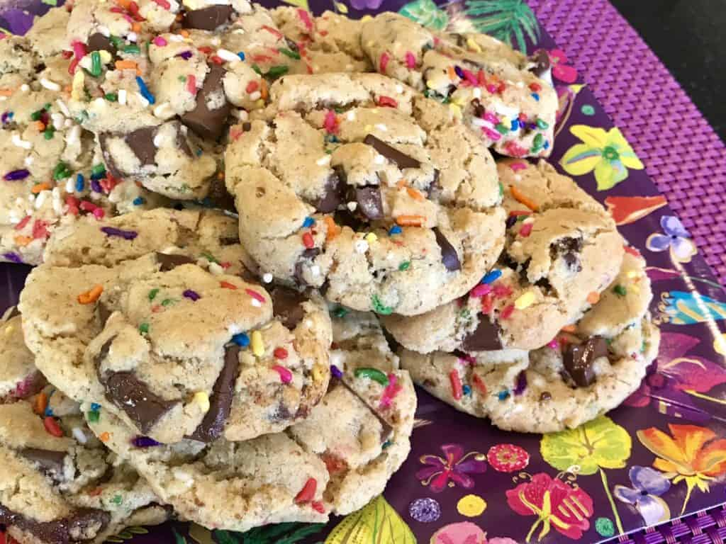 A pile of vegan funfetti chocolate chunk cookies on a plate