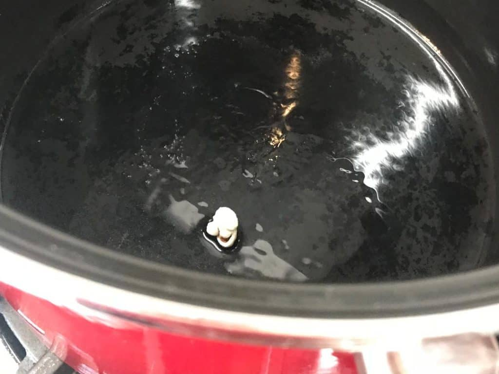 One popped popcorn kernel in a pot with oil