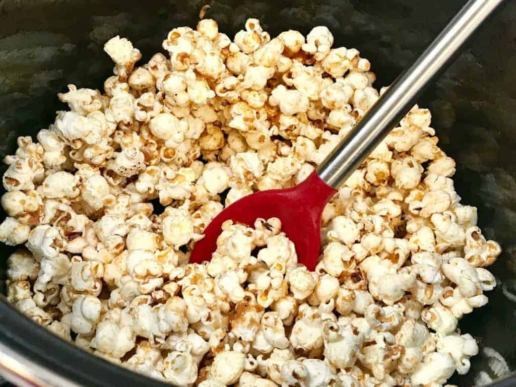 Kettle corn in a pot on the stove with sugar mixed in