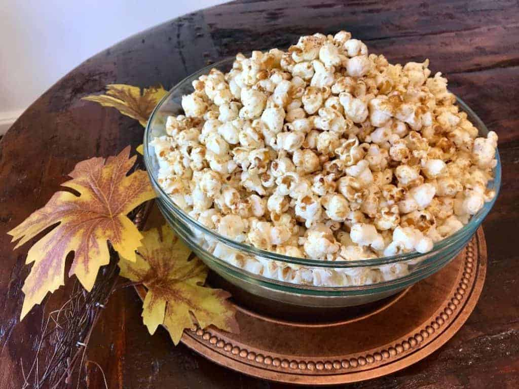 Kettle corn in a bowl on a serving platter next to decorative leaves
