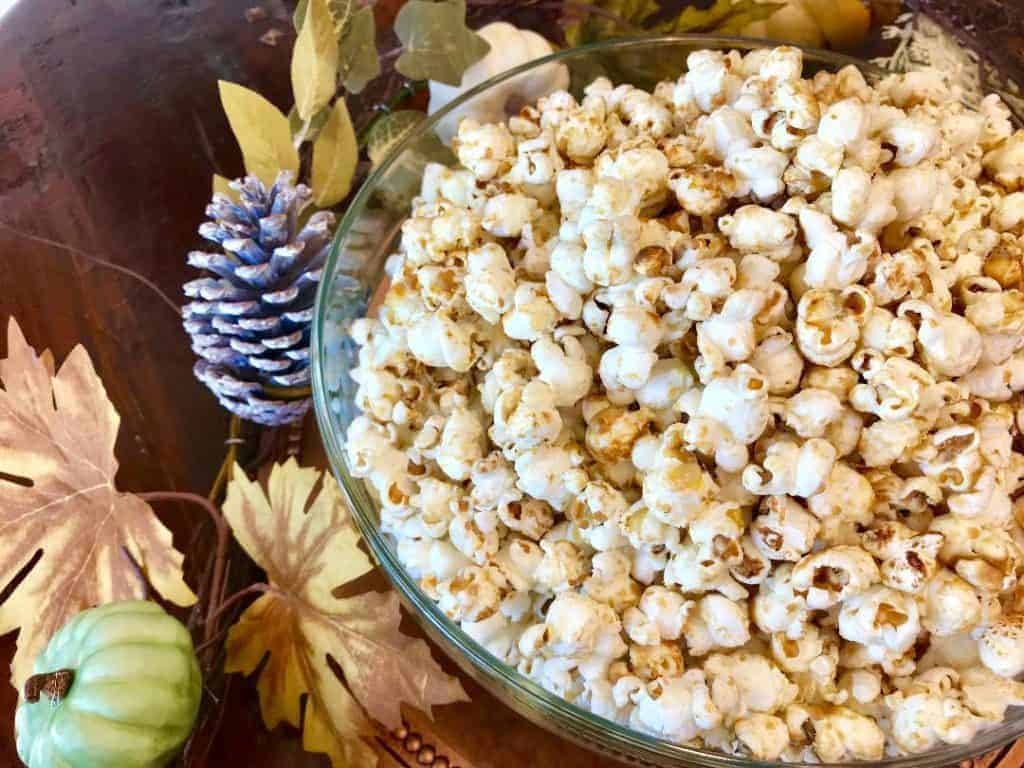Kettle corn in a bowl next to decorative leaves and pinecones