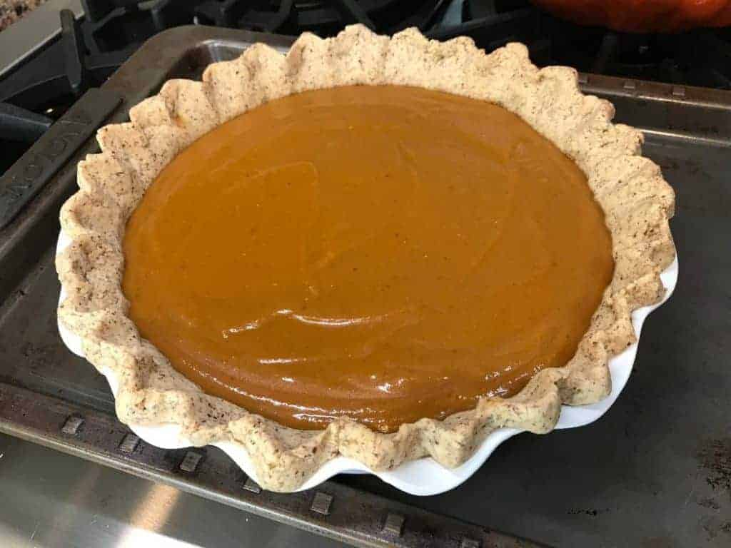 Pie crust filled with pumpkin pie filling before going into the oven