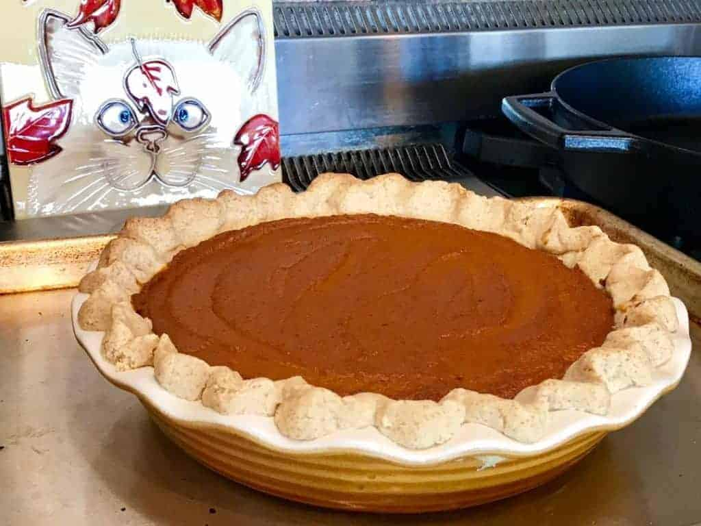 Baked pumpkin pie on a cookie sheet cooling