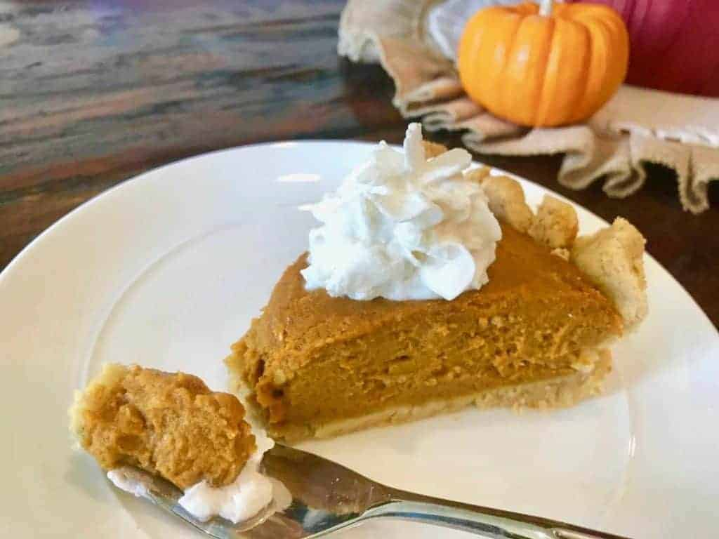 Piece of pumpkin pie with vegan whipped cream on a plate with a fork