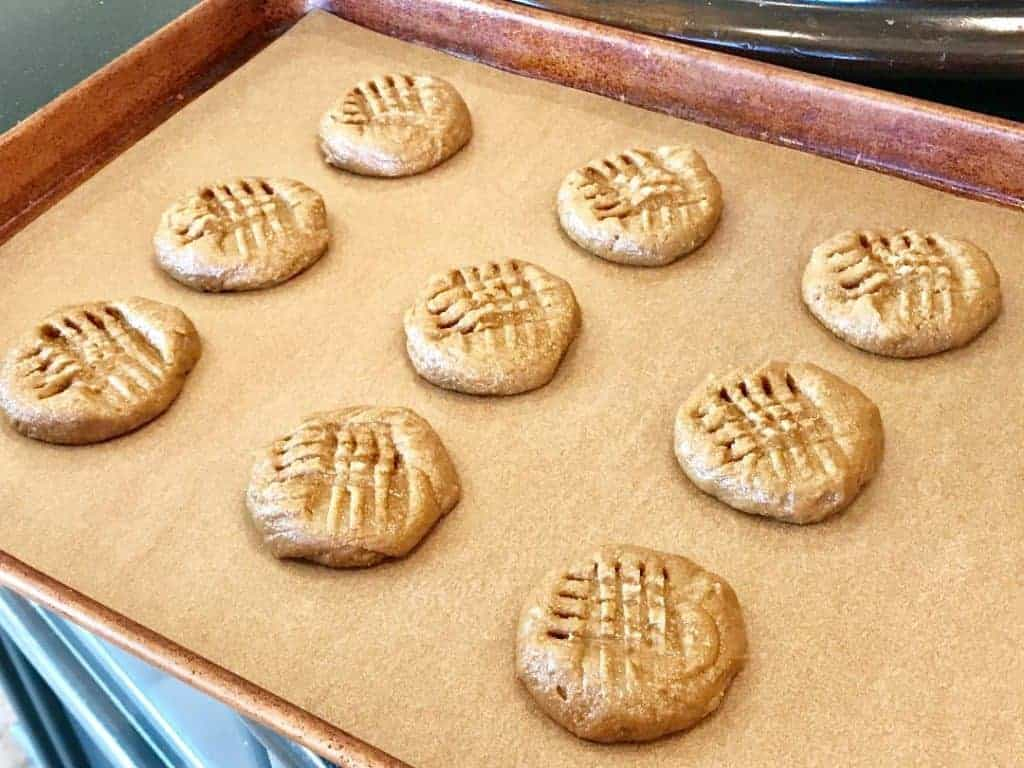 Baked peanut butter cookies on a cookie sheet