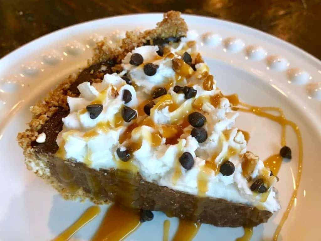 Pie of chocolate cream pie with pretzel crust on a plate with whipped cream, chocolate chips, and caramel drizzle