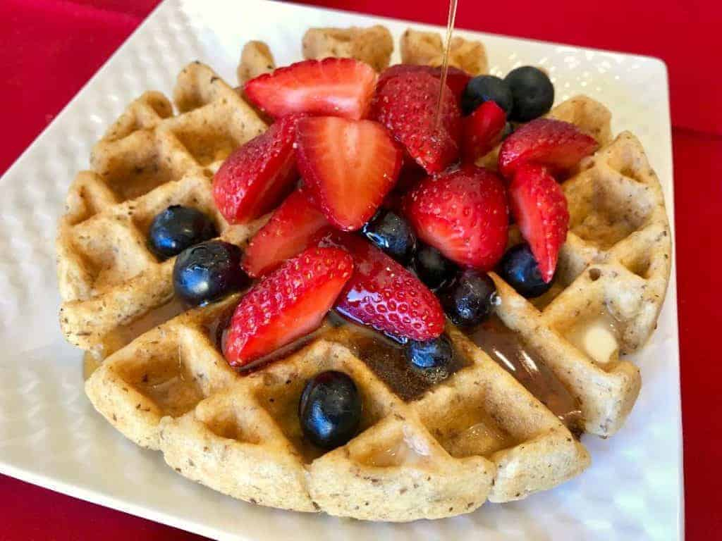 Vegan and Gluten Free Mixed Berry Oatmeal Waffles with Cinnamon Syrup on a plate with mixed berries